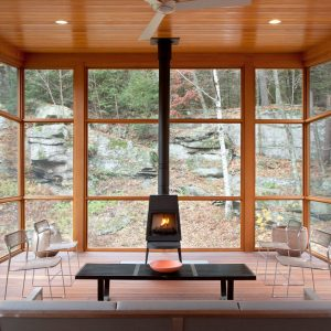 super-cozy-sunroom-filled-with-natural-wood-and-a-wood-burning-stove